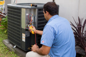 Standard Plumbing, Heating and Air doing maintenance on an air conditioner