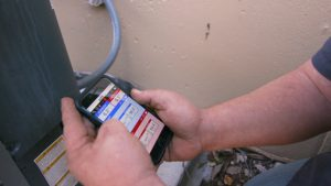Standard Plumbing, Heating & Air technician doing diagnostic testing on an outside air conditioner