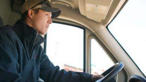 Standard Plumbing, Heating & Air plumber driving in tech van
