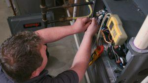 HVAC technician working on the wiring of a furnace inside a Manhattan, Kansas home