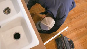 Standard plumbing working on the pipes underneath a kitchen sink in Manhattan, Kansas