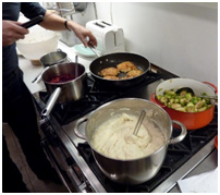 Stovetop with food cooking in a kitchen in Manhattan home