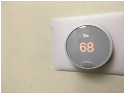 A round digital thermostat set to heat the home to 69 degrees.