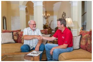 HVAC technician in home with man on couch shaking hands