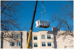 hvac unit being moved by crane for installation into commercial business