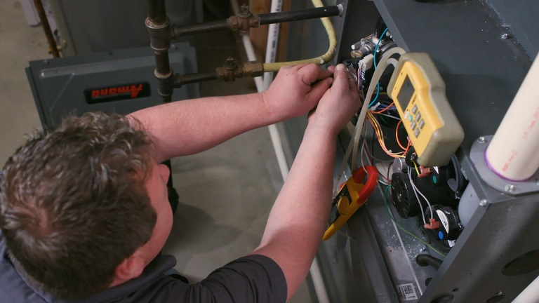 Standard heating technician working on diagnosing the problem of a broken furnace