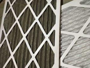 A dirty air filter next to a clean air filter
