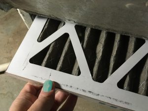 Removing a dirty air filter from a furnace and its time to buy air filters