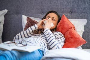 Woman suffering with allergies laying in bed needing improved indoor air quality services